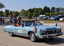 Blue car with Shriners decals and American flag