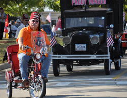 Man with fez in orange shirt on tricycle in front of a black car