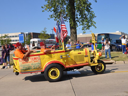 Yellow three-wheeled car with American flag and Shriners decals